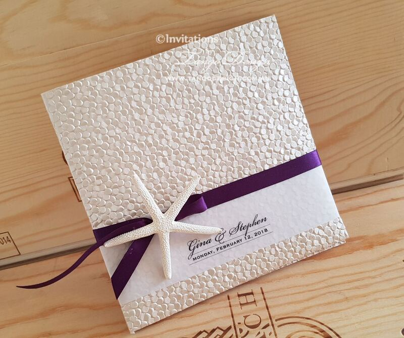 pebble pocket wedding invitation set with starfish and purple ribbon